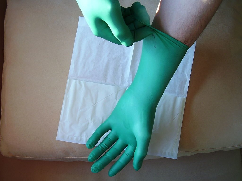 Person putting on latex gloves