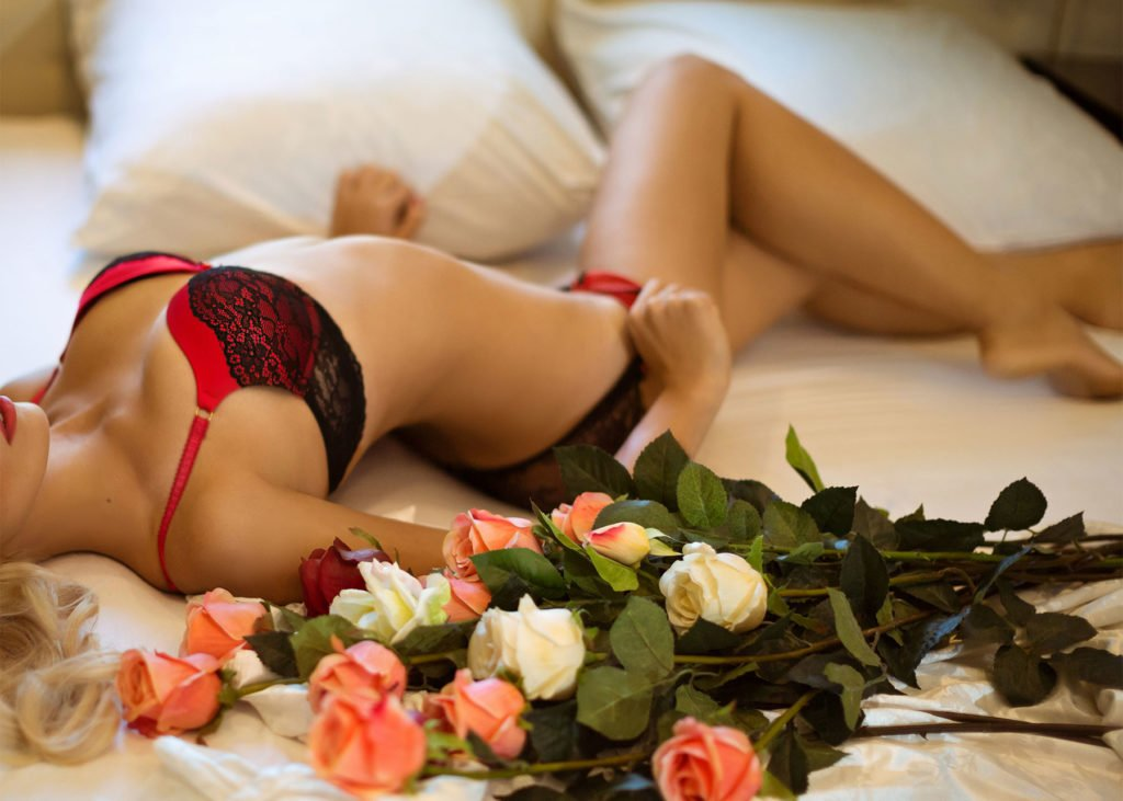 Sexy woman lying next to roses - escort and client role play scenario