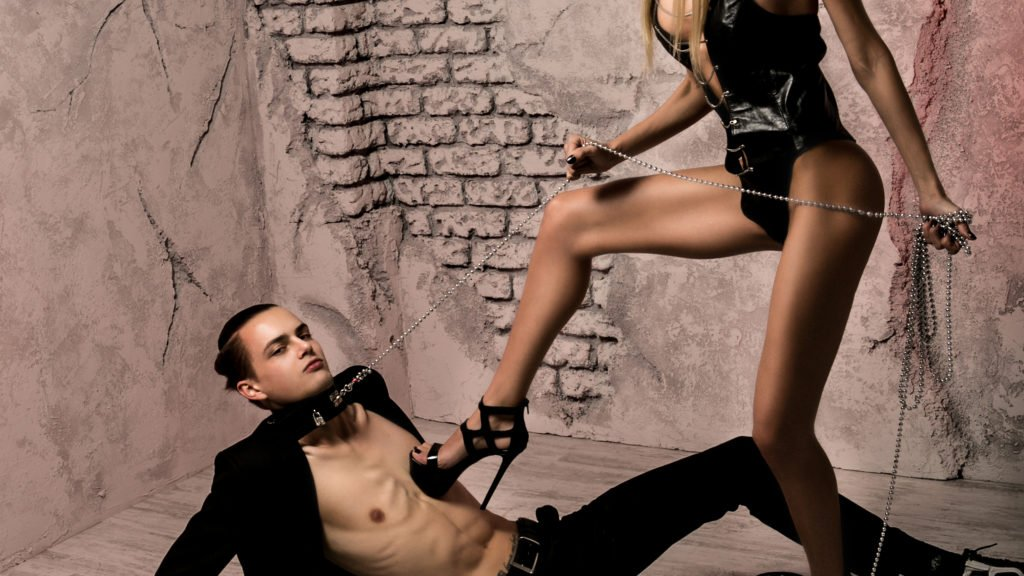 Man in bondage gear on floor; woman with high heel pressed into his chest